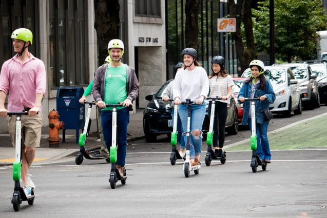 people riding electric scooters on a street