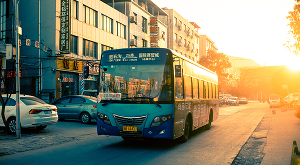 City bus driving down paved road at sunset