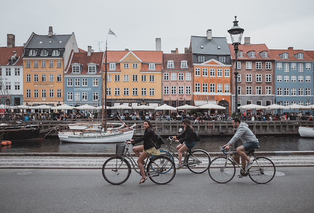 Three people ride bikes with a canal and buildings in the background
