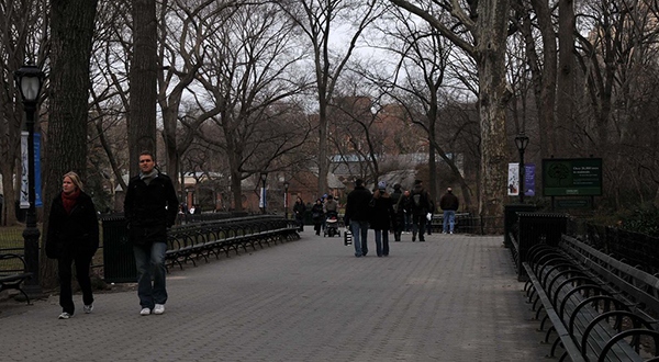 Path through Central Park in New York City with people walking past bare trees during overcast day