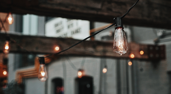 Bare light bulbs hanging from wooden beams in front of grey warehouse