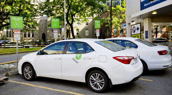 Two white ZipCars parked outside a building