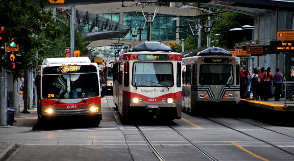 Two light rail trains and a bus parked next to each other on a city street