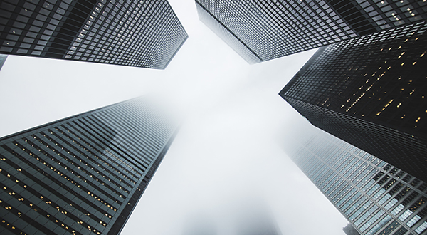 View looking up at tall buildings with some disappearing into fog