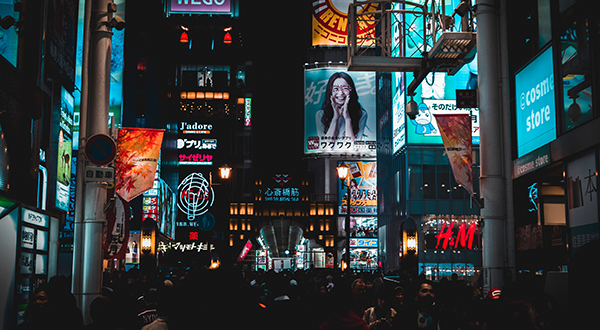 Crowded city square in Osaka, Japan at night with advertisements in the background