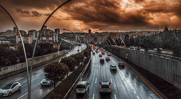 Cars driving on highway outside of city in Turkey with dramatic sky