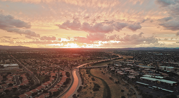 Drone image of sprawling city in Arizona with canal at sunset