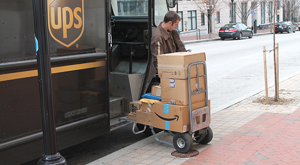 UPS driver unloading packages on city curb