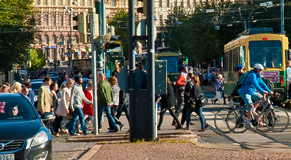 Pedestrians and cyclists crossing a busy street with cars and light rail