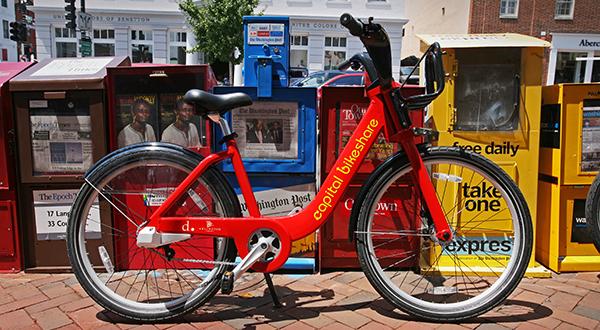 Bikeshare bike on sidewalk in front of newspaper boxes