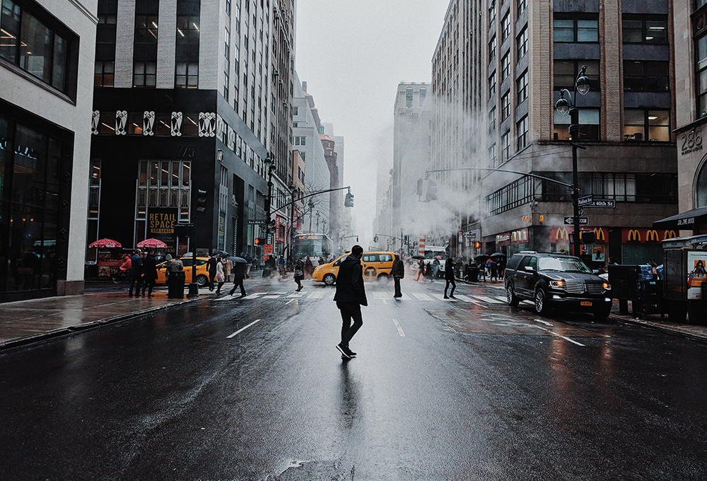 Man crosses wet city street in front of crosswalk with cabs and pedestrians in the backround