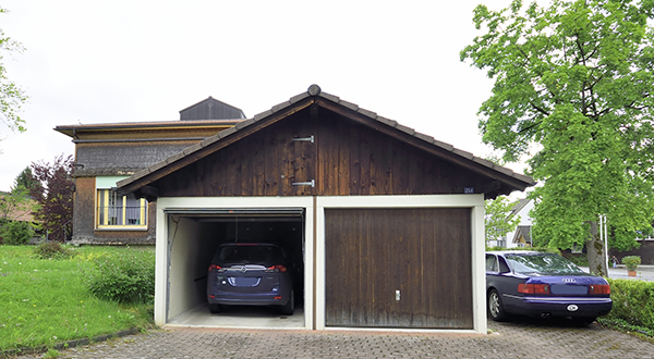 Blue car in a two-car garage with another blue car parked nearby
