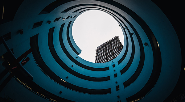 Looking up from interior gap of a spiraling parking garage toward the sky