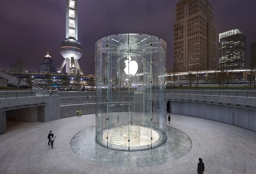 Stairway leading below ground within a glass cylinder with an Apple symbol with a city in the background