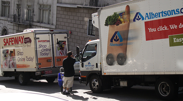 A man stands between two grocery delivery trucks