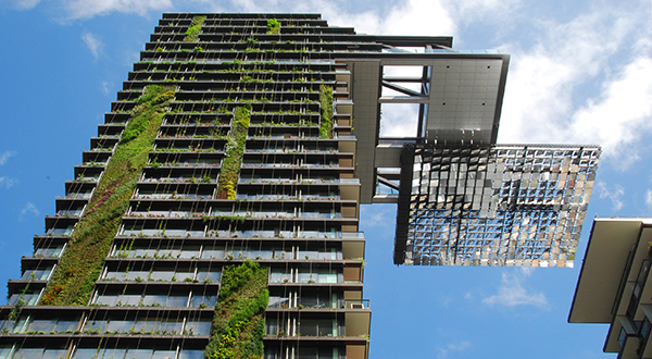 Skyscraper with plant strips on its side with solar mirror