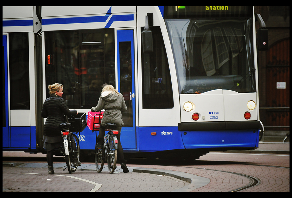 two women on bikes waiting for bus to pass