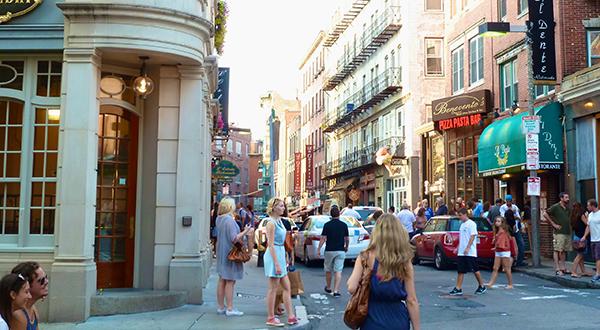 People between buildings on a street