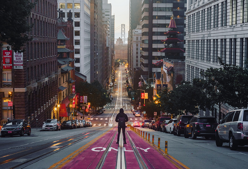 Man stands in middle of city street with train tracks in San Francisco