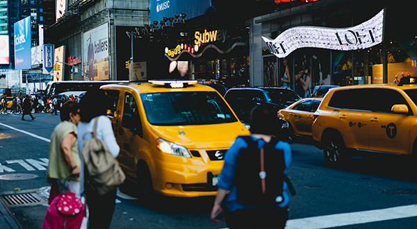 Pedestrians standing by a taxi in Times Square, New York City