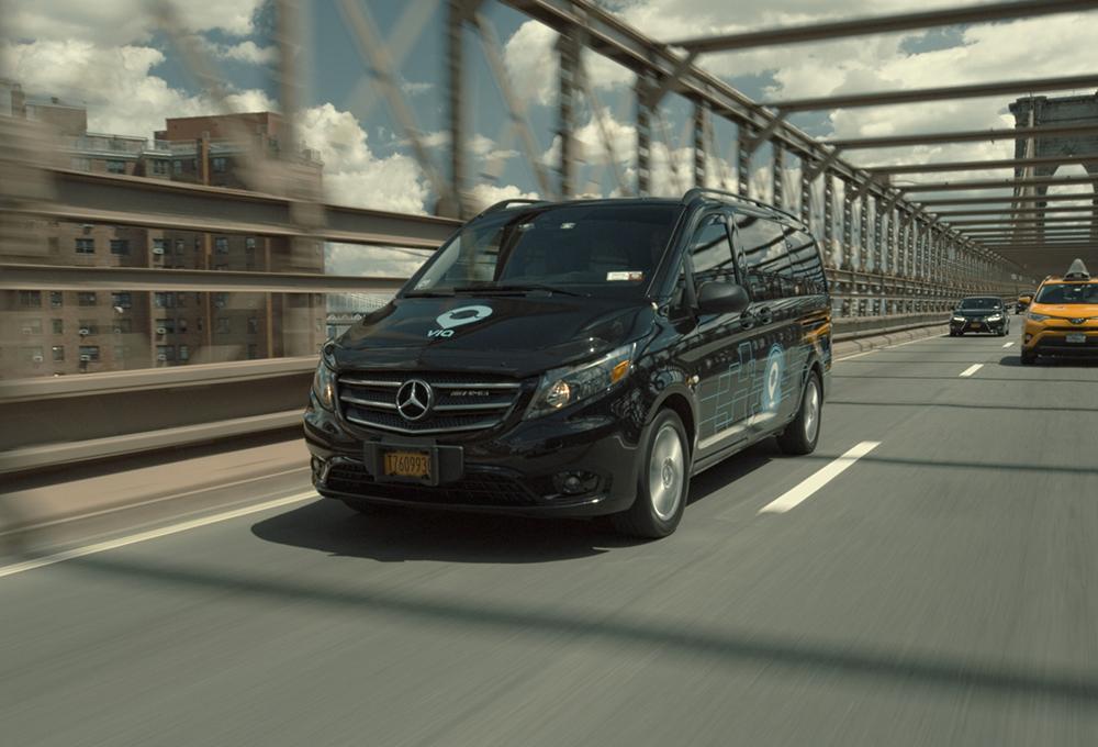 Black microtransit van driving across bridge