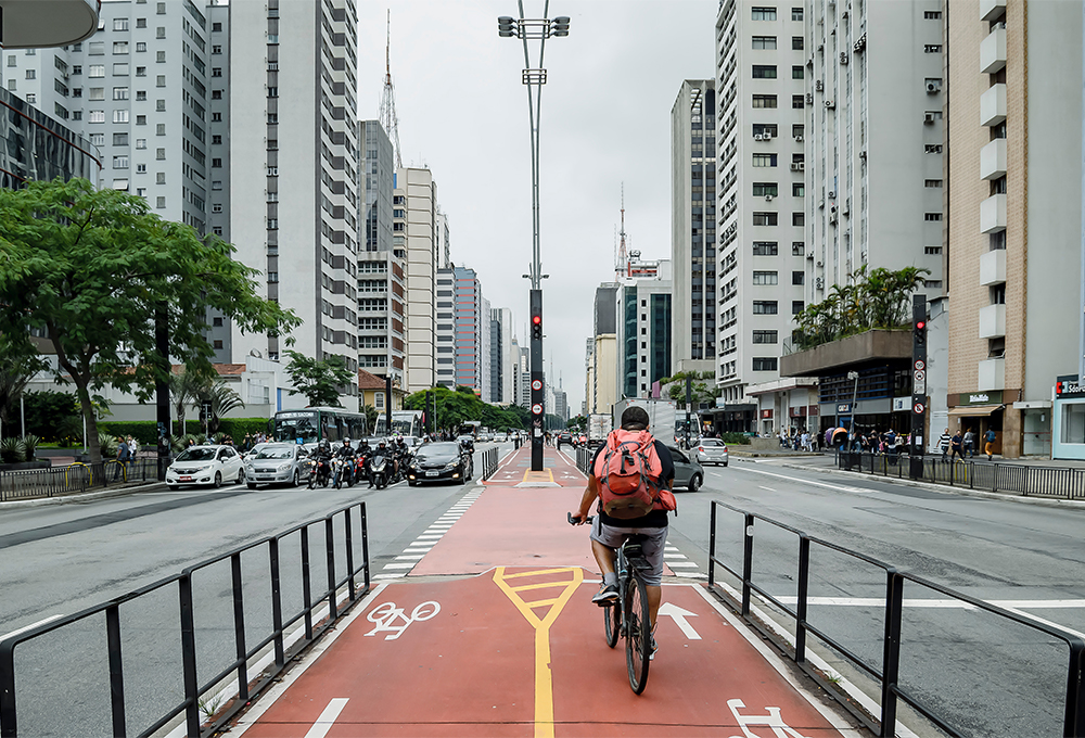 Bicyclist riding on protected red bike lanes in the center of busy street in Sao Paulo, Brazil