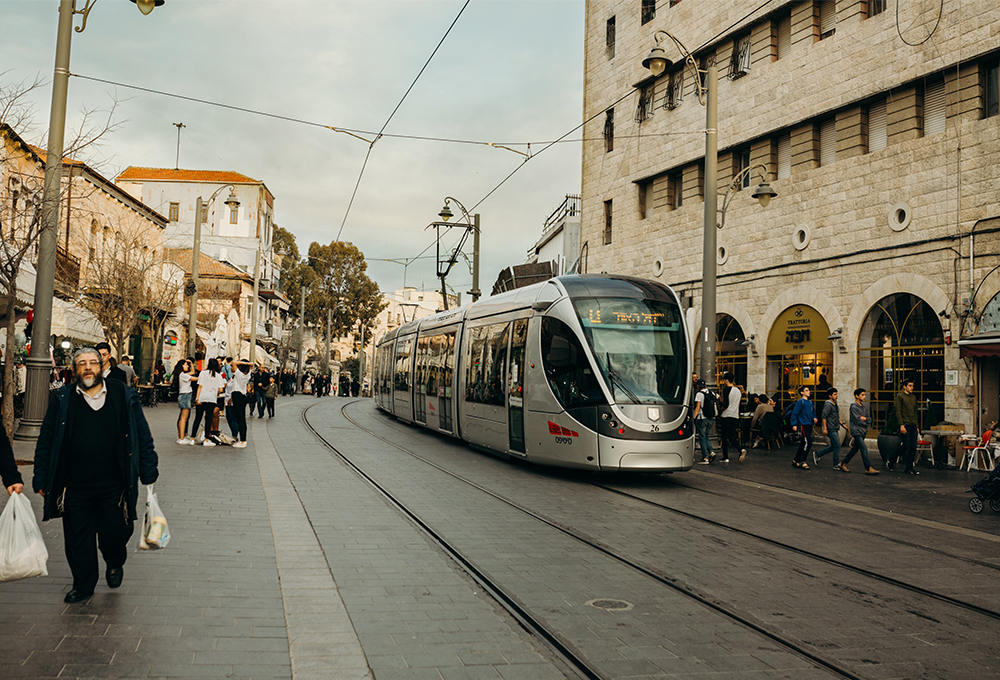 people walking next to light rail and buildings in Jerusalem