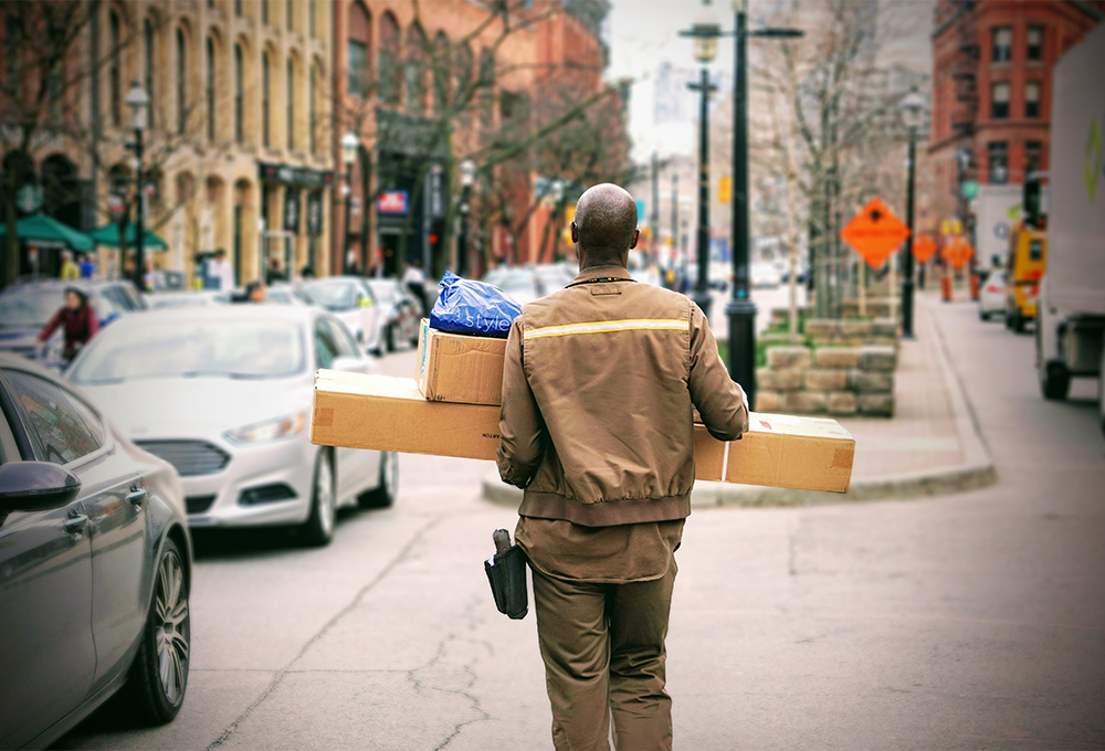 Delivery man carrying packages through city