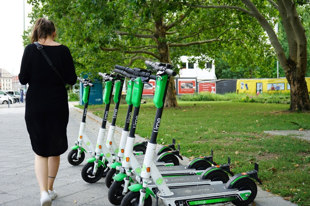Woman walking by e-scooters lined up