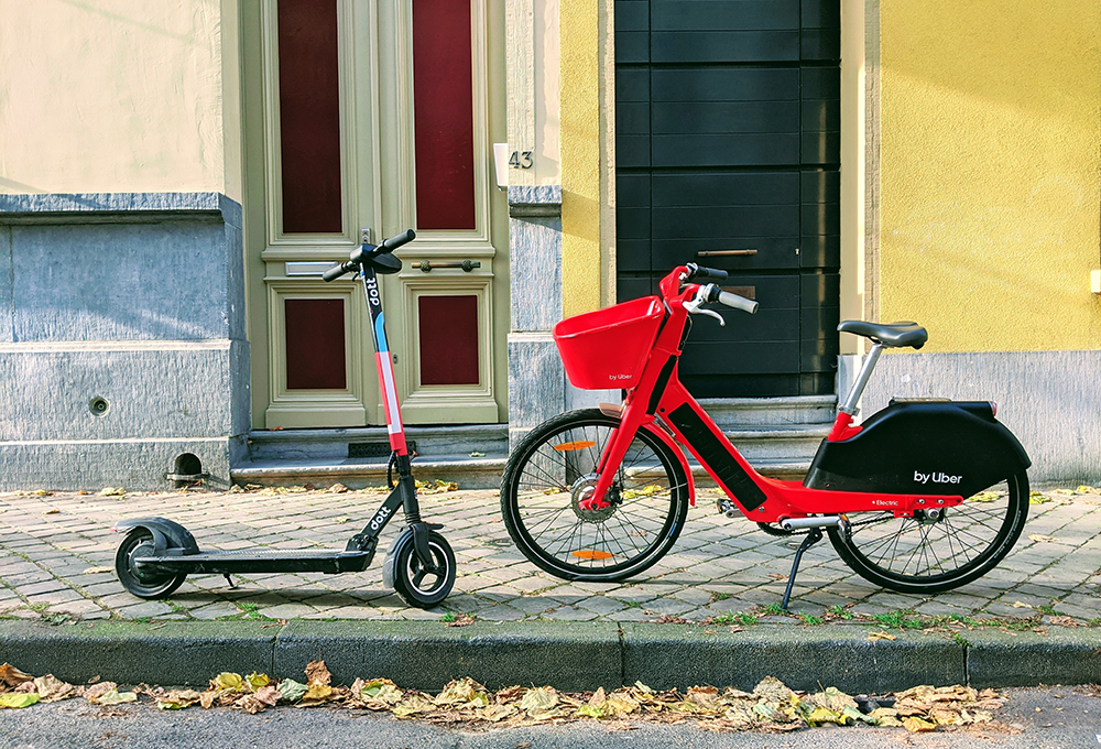 electric scooter and bikeshare bike parked on a sidewalk
