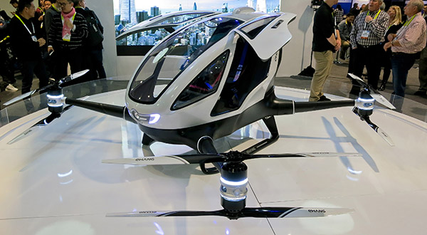 A landed aerial passenger drone with doors open in the middle of a showroom