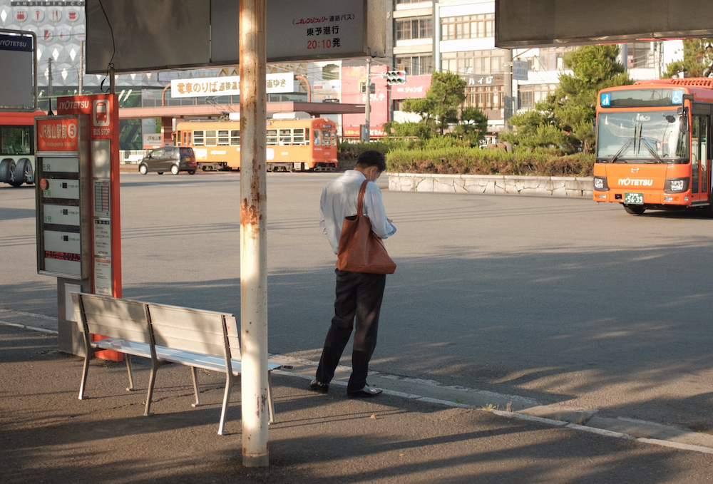 Photo of man on cell phone waiting at a bus depot.