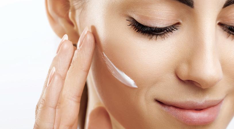 Woman moisturising her face