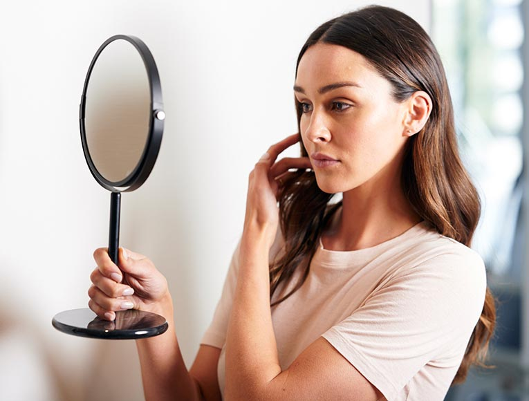 woman looking at her face in a small hand held mirror