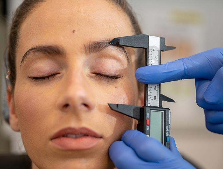 dermal clinician assessing client's skin