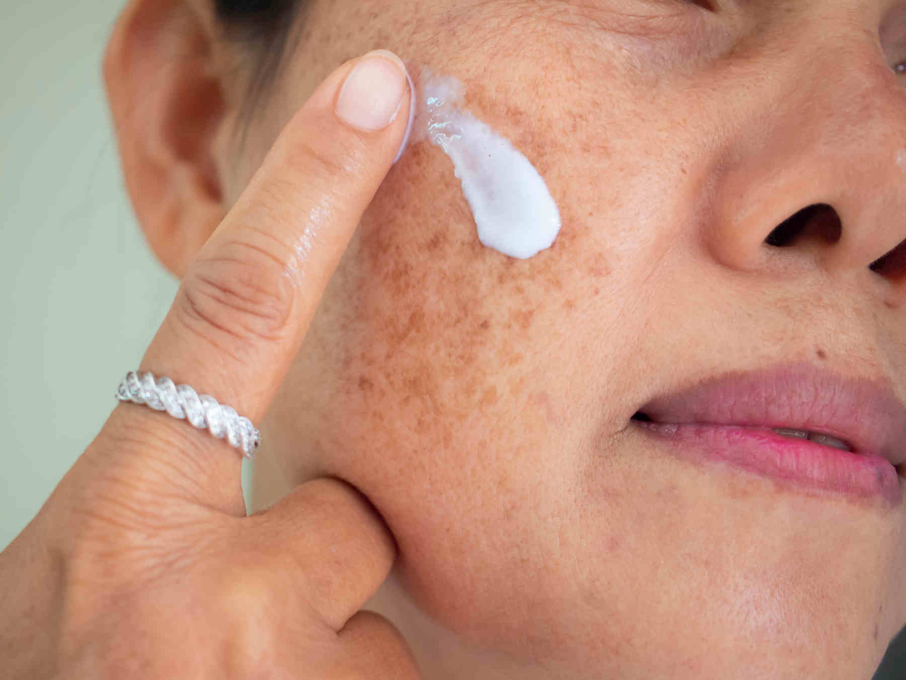 women applying cream on her face