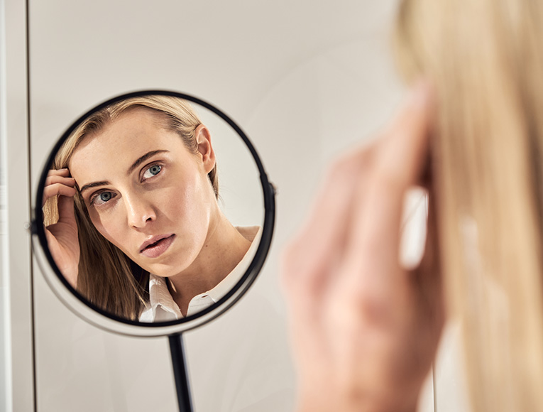 woman looking at her skin in the mirror