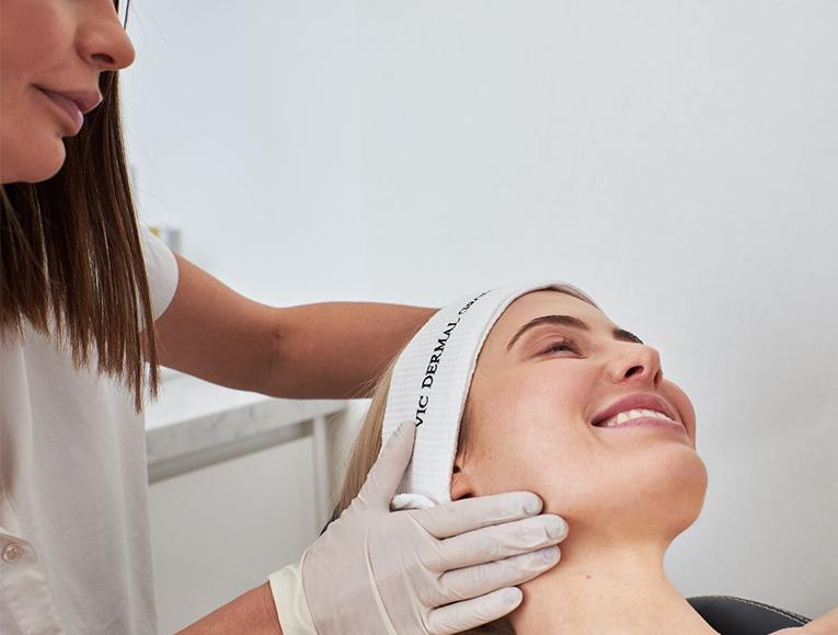 dermal clinician touching client's skin during skin treatment