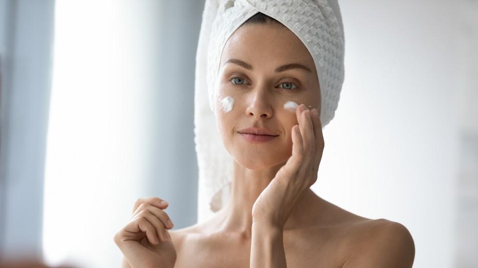 Woman applying sunscreen in bathroom mirror