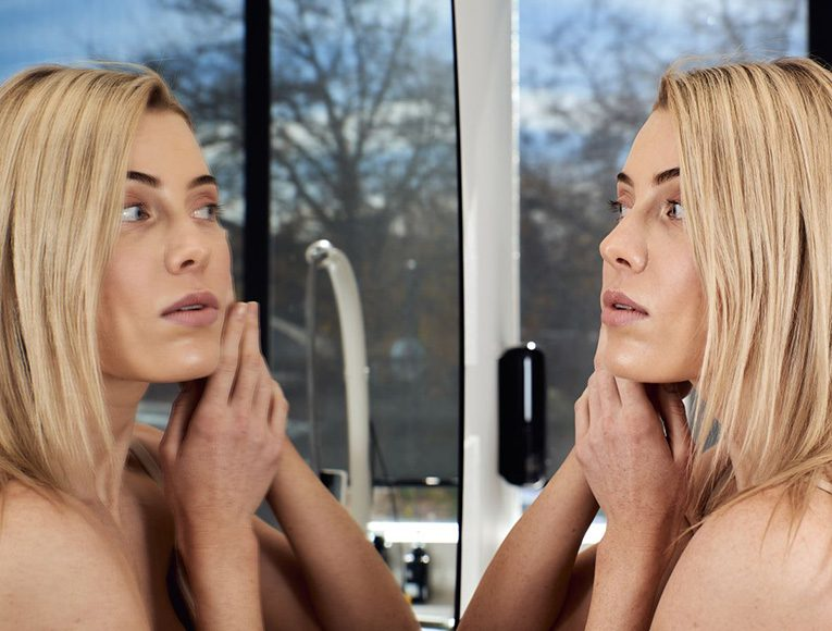 woman looking up close at her face in her bathroom mirror