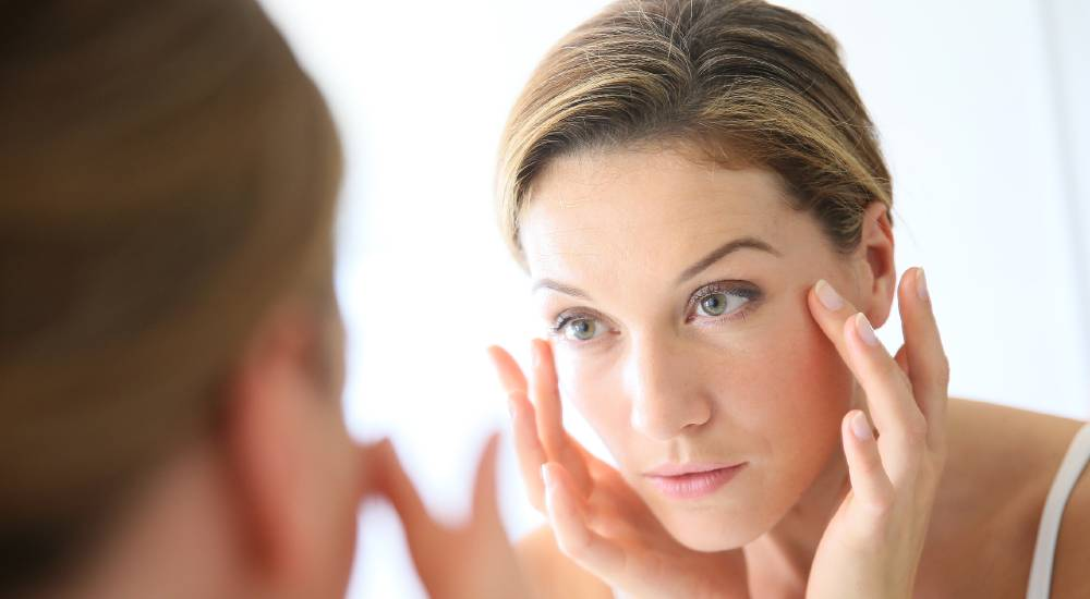 Woman inspecting her face in a mirror