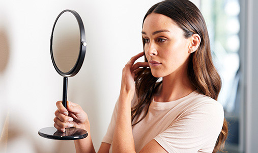 woman looking at her skin in a mirror