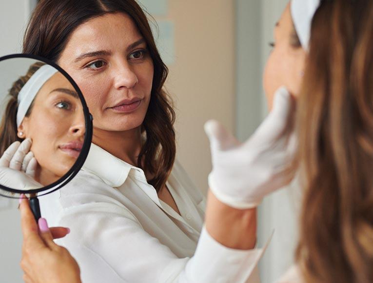 dermal clinician examining client's skin