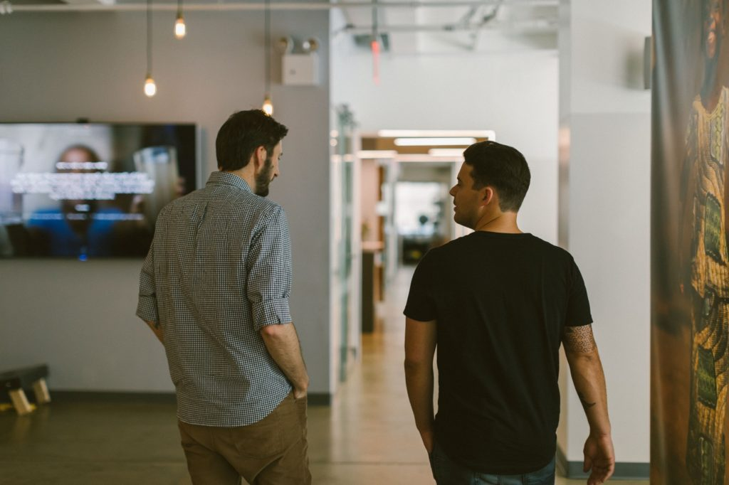 Photo of two men walking away from the camera toward a hall. On the left is a television, and a man with a dark beard and short hair wearing a checkered button-down. To his right is another man with short dark hair wearing a black t-shirt.