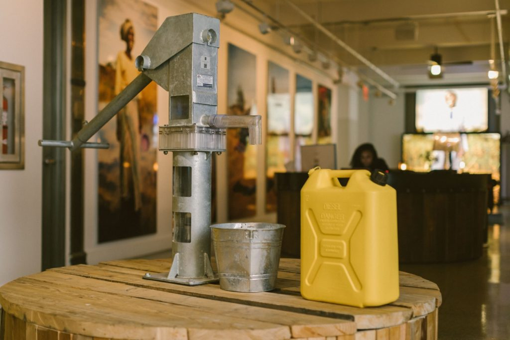 A wooden well with a metal pump and a plastic yellow water jug take center stage at charity: water's headquarters