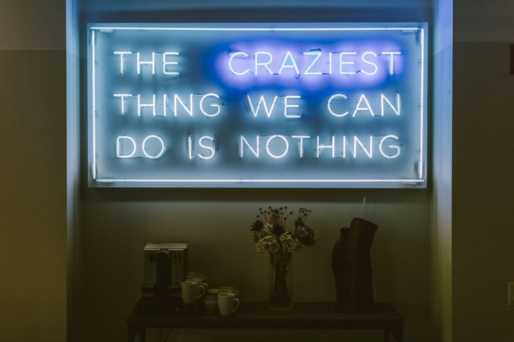 blue and purple neon sign saying THE CRAZIEST THING WE CAN DO IS NOTHING.
