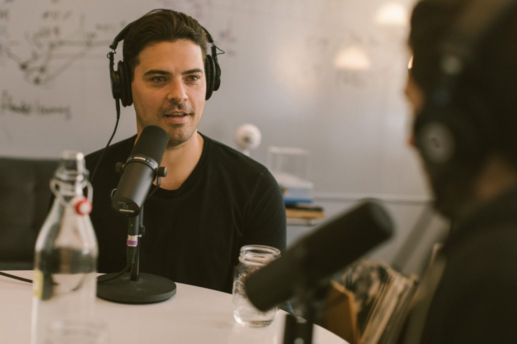 A photo of a man wearing headphones and speaking into a microphone. He has a bottle in front of him, but it's out of focus.