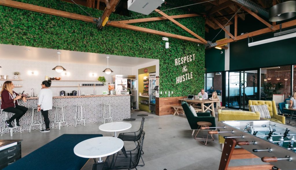 "A coworking space with a foosball table in the bottom right corner, chairs and a kitchen bar, and a green wall with the words ""Respect the hustle""."