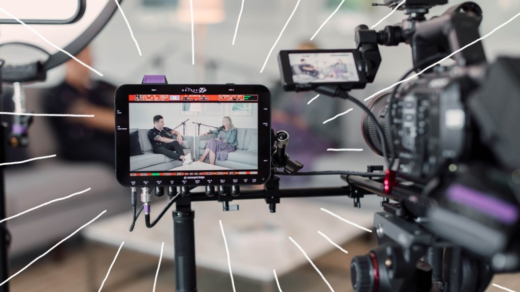 Looking at the viewfinder of a digital video camera and second camera. The cameras are focused on Erin and Justin sitting on a couch. There are doodled white lines radiating off of the camera.