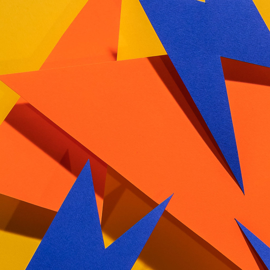 Orange and blue construction paper shapes with sharp angles on bright yellow background